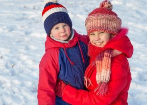 kids in winter clothing to keep warm ice fishing